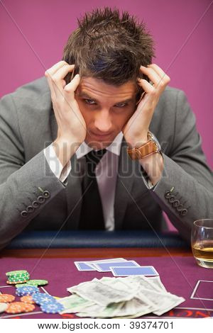 Depressed man sitting in a casino at table while playing poker