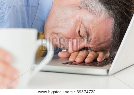 Businessman holding coffee and sleeping on his laptop on his desk