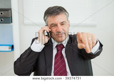 Businessman phoning and pointing sitting at his desk in his office