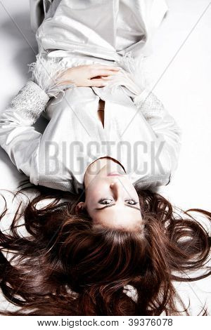 young elegant woman in silver dress lie on the floor studio shot