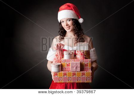 Santa girl is holding Christmas gifts.