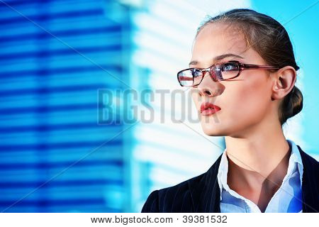 Young business woman standing in the big city and purposefully looking away.