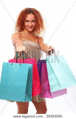 Beautiful redhead woman holding shopping bags