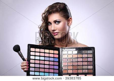 Beautiful and glamour woman with makeup color palette and brush