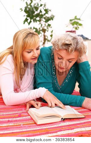 Granny and granddaughter reading a book on a red mat at home