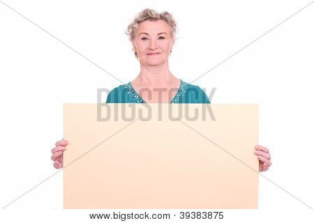 Smiling granny with emty poster in hands over a white background