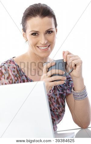 Portrait of smiling woman with coffee mug handheld sitting with computer, looking at camera,