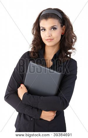 Pretty young businesswoman holding laptop, looking at camera.