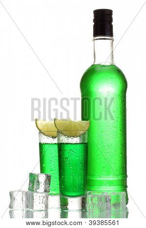 bottle and glasses of absinthe with lime and ice isolated on white