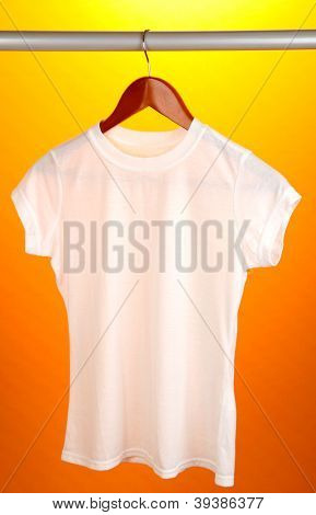 White t-shirt on hanger on orange background