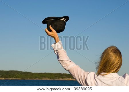 Person Waving With Hat In Front Of The Sea
