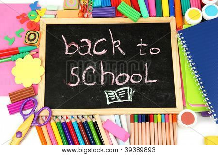 The words 'Back to School' written in chalk on the small school desk with various school supplies close-up