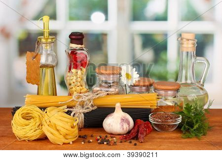 Pasta spaghetti, vegetables and spices on wooden table on bright background