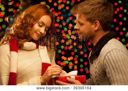 young happy smiling casual couple making a present