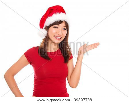 Asian Christmas woman presenting / showing copy space standing in Santa hat. Isolated on white background smiling looking at camera.
