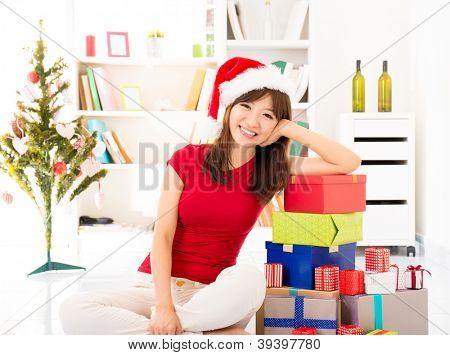 Happy Asian female leaning on stack of Christmas gift, preparation of Christmas day.
