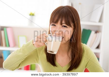Young Asian woman drinking a glass of soy milk at home