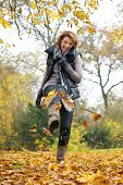 stock photo of mid autumn  - A woman kicking yellow leaves in autumn - JPG