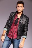 fashion model in casual clothes and leather jacket standing on gray background