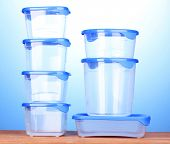 pic of tupperware  - Plastic containers for food on wooden table on blue background - JPG