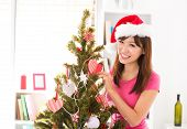 Beautiful Asian woman decorating Christmas tree in her house