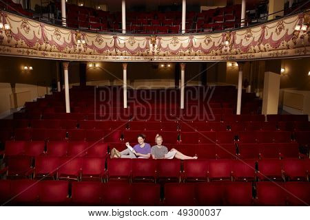 Full length portrait of two young women sitting in theatre stall with scripts