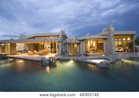 Swimming pool and illuminated modern house exterior against the sky
