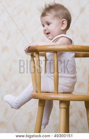 Side view of a playful baby boy sitting on high chair