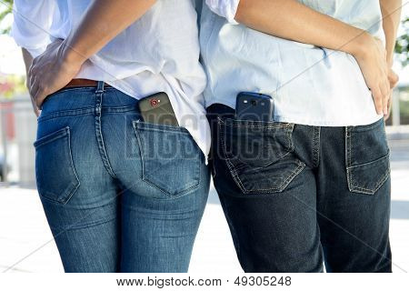 Back Portrait Of Young Couple With Mobile In The Pocket