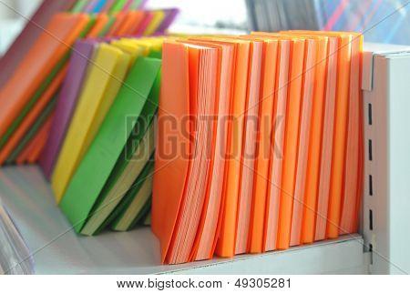 On shelf each kind of color notebook
