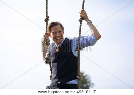 Smiling Businessman Swinging In Ropes