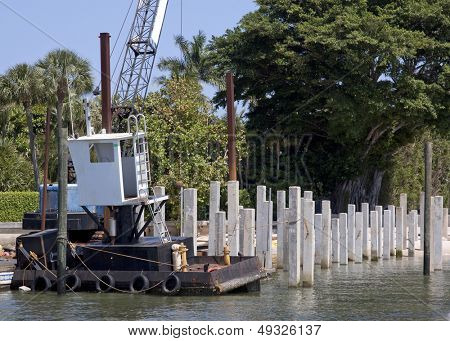 An white construction crane sits on a floating platform in the Intracoastal Waterway at the end of a pier that is being rebuilt.