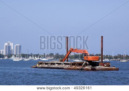 An orange construction crane sits on a floating platform in the Intracoastal Waterway.
