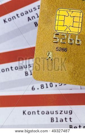 a gold credit card and bank statement .. symbolic photo for cashless transactions and status symbols.