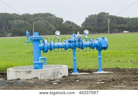 Irrigation pipes in front of green field