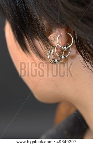 a girl's ear with lots of earrings