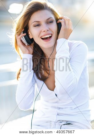 Delightful young woman taking her headphones off