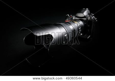 Professional digital photo camera with zoom lens on black background