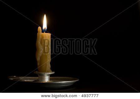 antikes Metall Candlestick mit brennenden Kerze auf schwarz Hintergrun