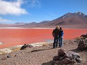 picture of eduardo avaroa  - Young tourist couple admiring the Red Lagoon or Laguna Colorada on the Altiplano near Uyuni inside Eduardo Avaroa National Reserve in Bolivia at 4300 m above sea level - JPG