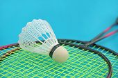 stock photo of game-cock  - Shuttlecock and badminton racket on blue background - JPG