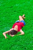Beautiful young  slim woman relaxing lying on the grass