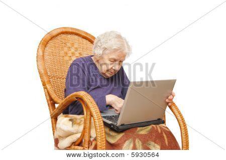 Abuela con el portátil en un sillón