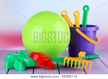 Bright ball and sandbox toys on table on bright background