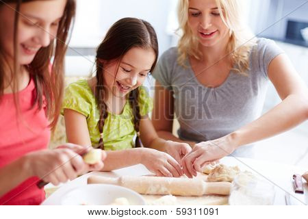 Portrait of happy girls and their mother cooking pastry in the kitchen