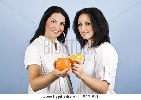 Two Young Women Drinking Citrus Juice