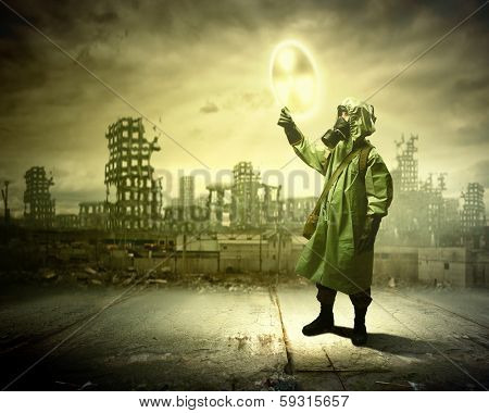 Image of man in gas mask and protective uniform touching radioactivity sign