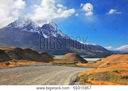 Dreamland Patagonia. Snow-capped mountain peaks, the lake and the gravel road