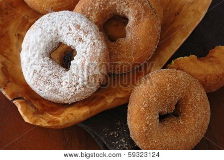 Cinnamon and powdered sugar donuts on wooden serving tray.  Rustic still life with directional, natural lighting for effect.