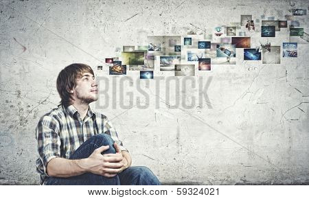 Young man in casual sitting on floor and looking at media photos